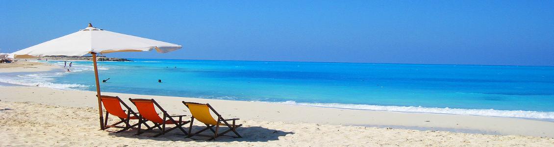 En sandstrand med tre solstolar på Mallorca.